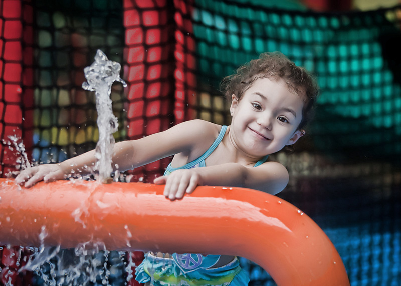 Young girl playing in water structure