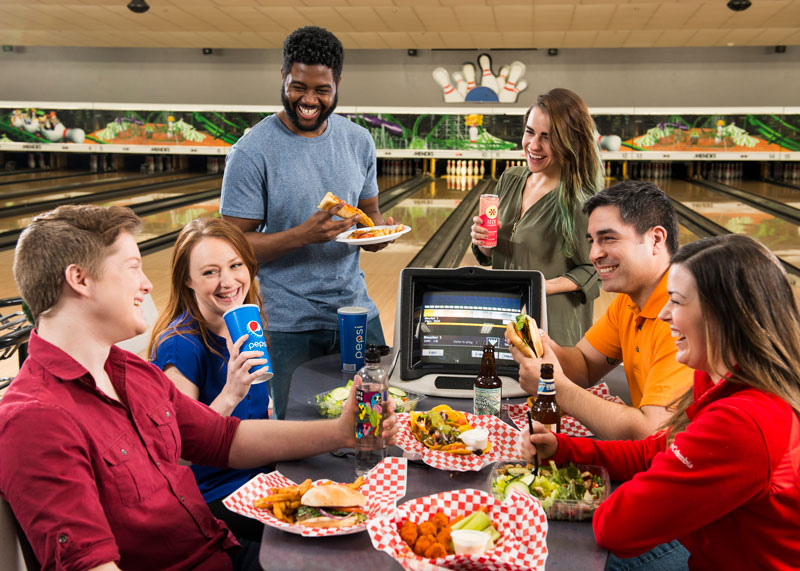People eating food at a table in a bowling alley