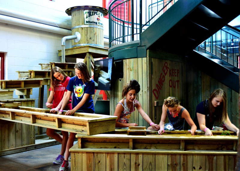 Young girls panning for fossils in mining sluice