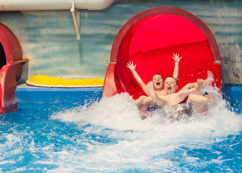 Young kids sliding down red waterslide