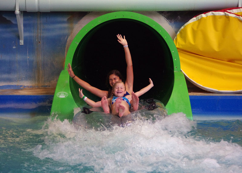 Young kids sliding down a green waterslide