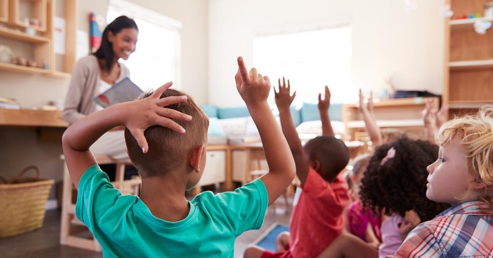 Kinder heben die Hände in der Schule