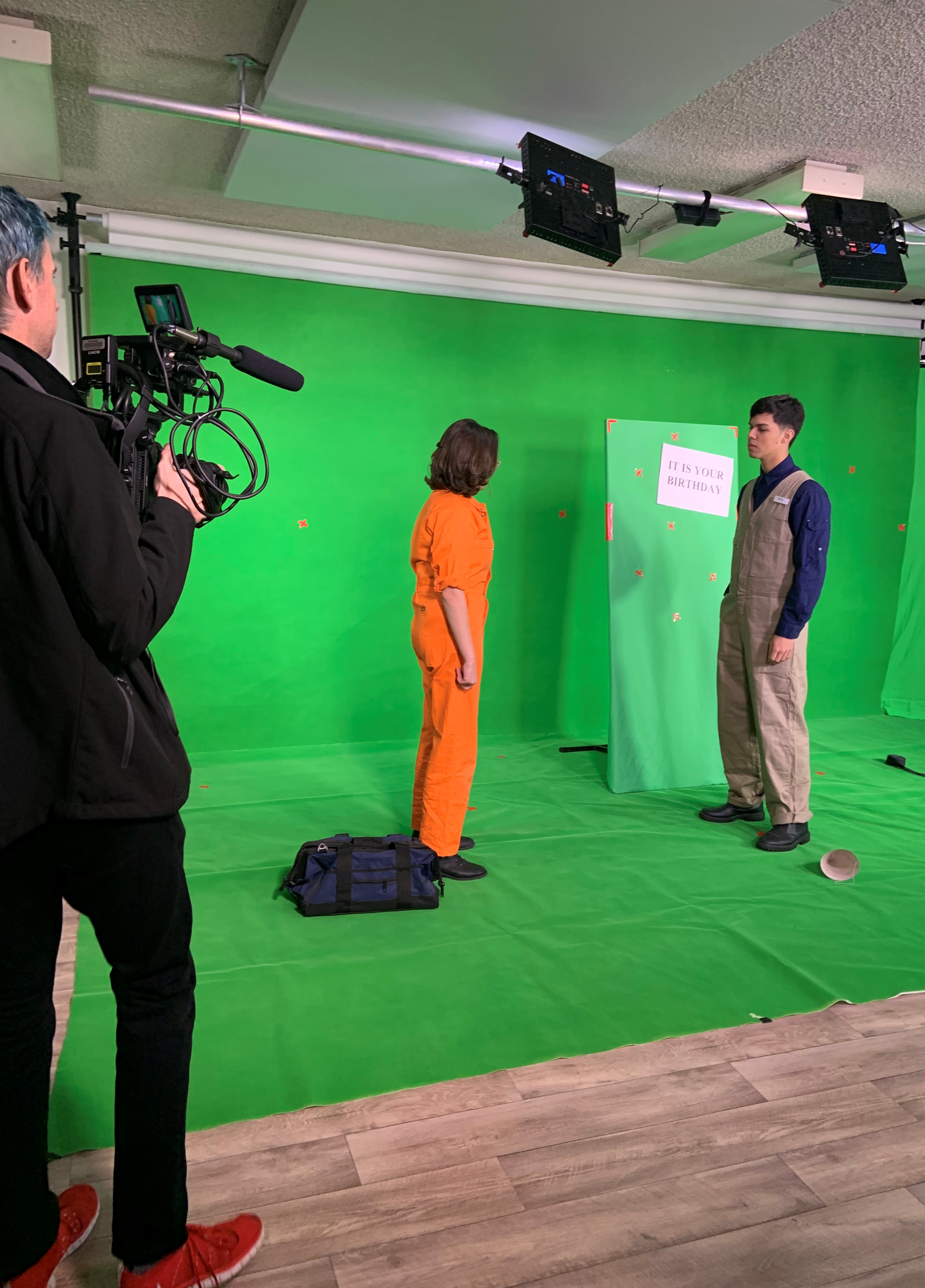 Two actors facing each other and being filmed in front of a green screen