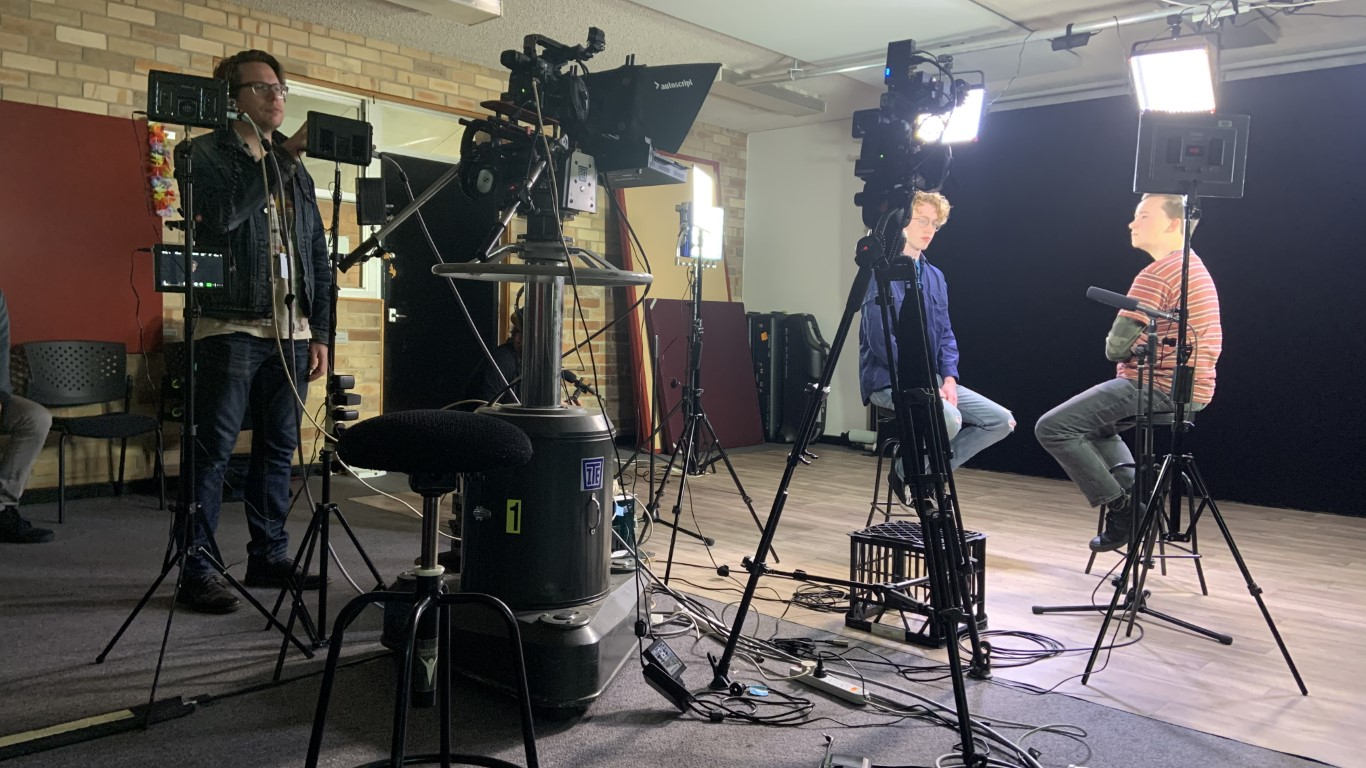 Two actors in a filming studio with a cameraman looking at a monitor.