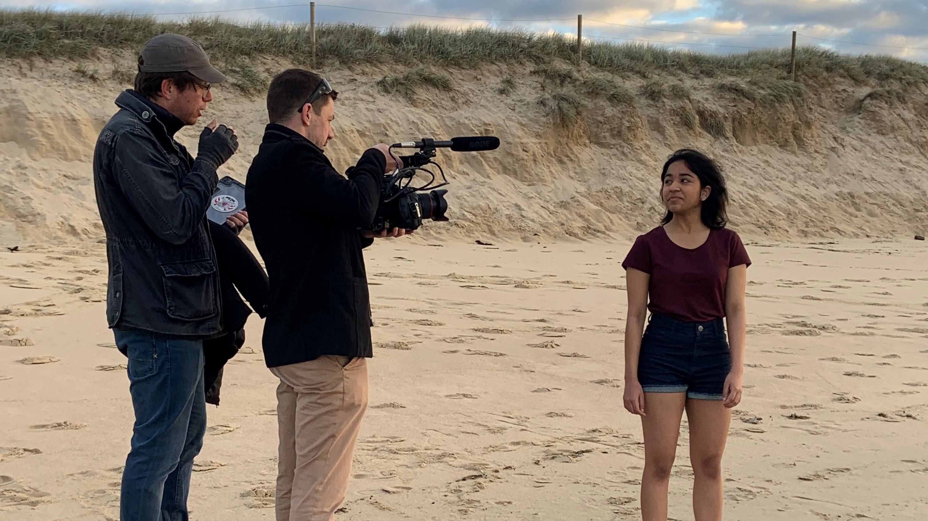 A camera man and his assistant filming an actor on a beach.