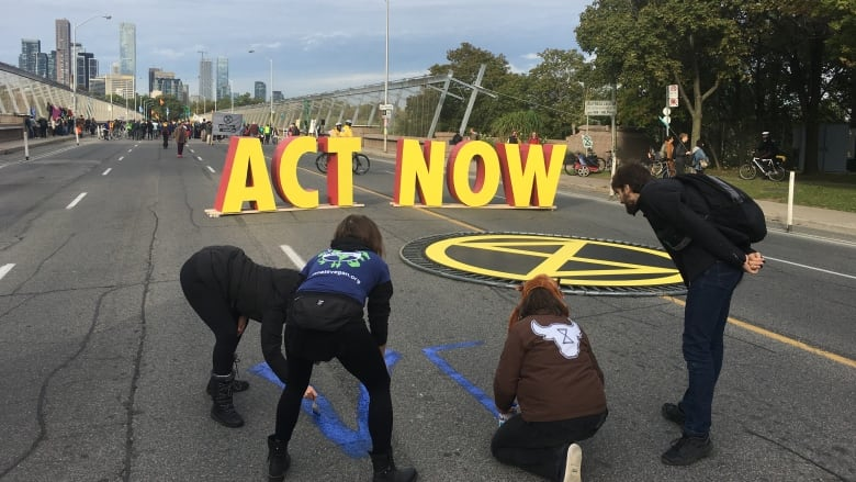 Demonstrators painted the roadway on the Bloor Viaduct during the shutdown Monday. (Mark Bochsler/CBC)