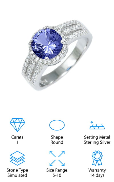 This round tanzanite ring is a gorgeous example of the halo ring design. The 10 mm center stone is surrounded by smaller cubic zirconia stones. And even more, there are three lines of smaller white stones running down the thick band on either side of the halo. The effect is a sublimely sparkling ring that is sure to make whoever you choose to gift it to happy. All of these stones are set in sterling silver that won't turn her fingers or oxidize. You'll have a beautiful ring for years to come with this option! We love how many stones are in this ring, and because they are heat-treated to preserve the color and shine, they sparkle extremely beautifully. This ring design is classic and beautiful, and it will go with just about any outfit that you decide to put together. It's versatile and beautiful, with a price point that you can't argue with! It's the perfect fit.