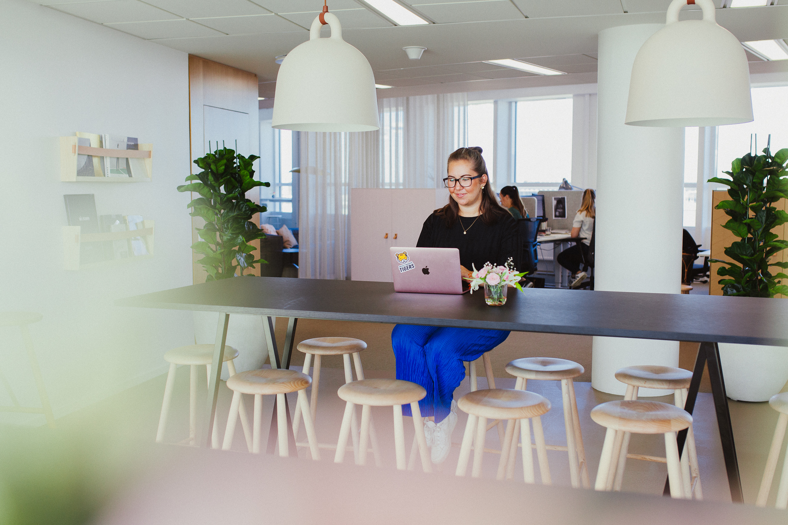 Project Manager Hanna working at a high table in the Malmö office