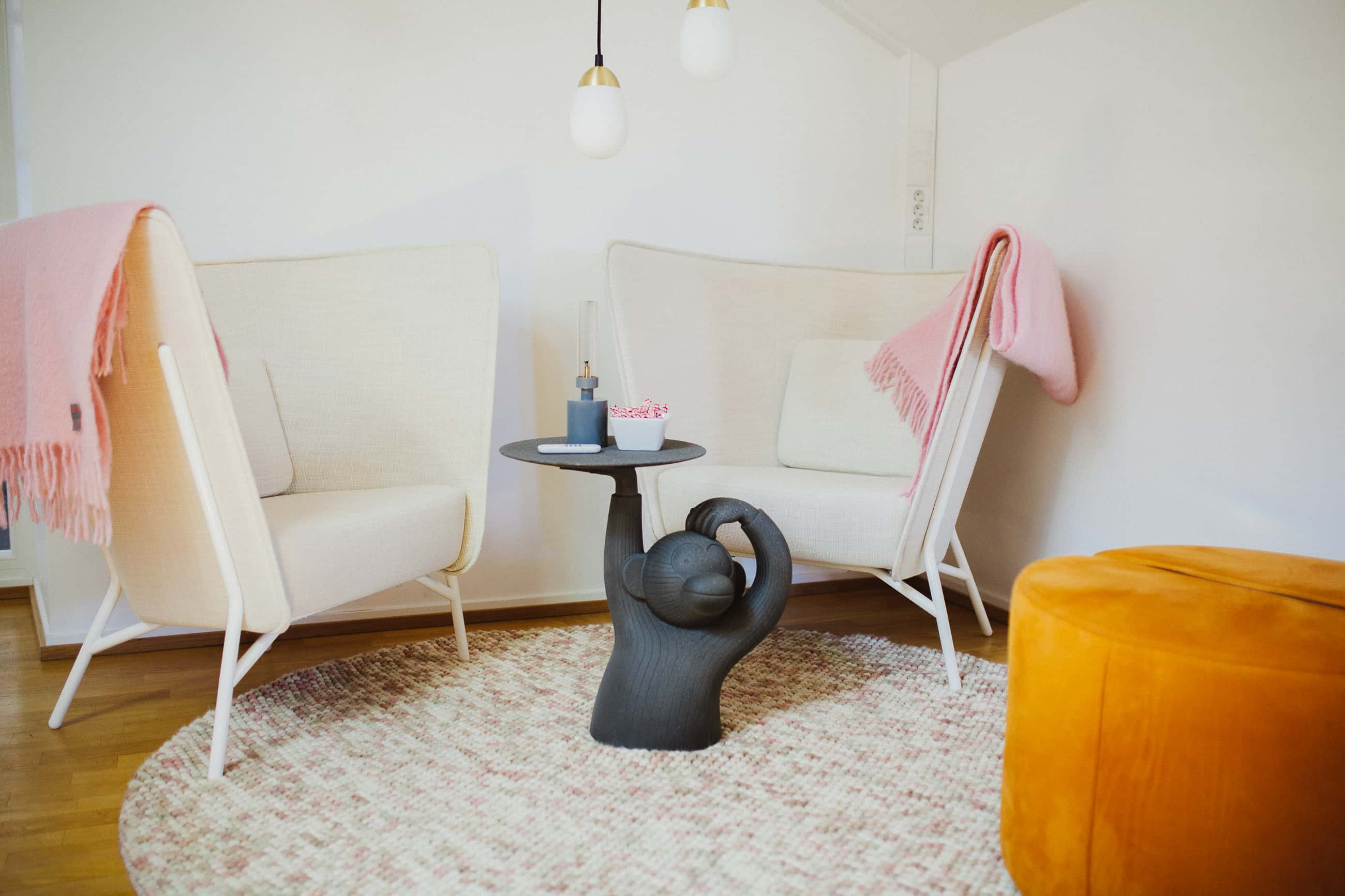 A lounge area with two chairs, an orange stool and a coffee table resembling a monkey.