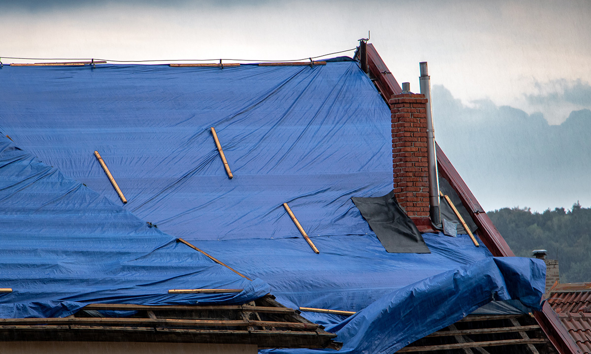 large tarp covering a section of a roof due to rain