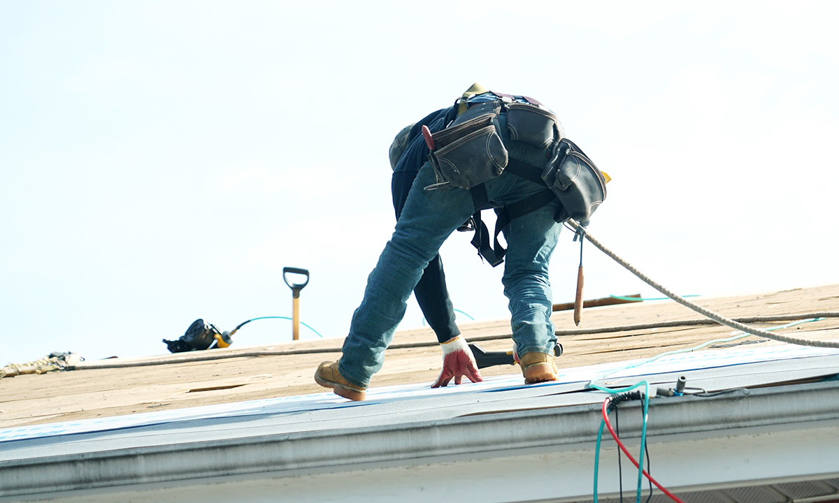 roofer installing underlayment with tools on a roof
