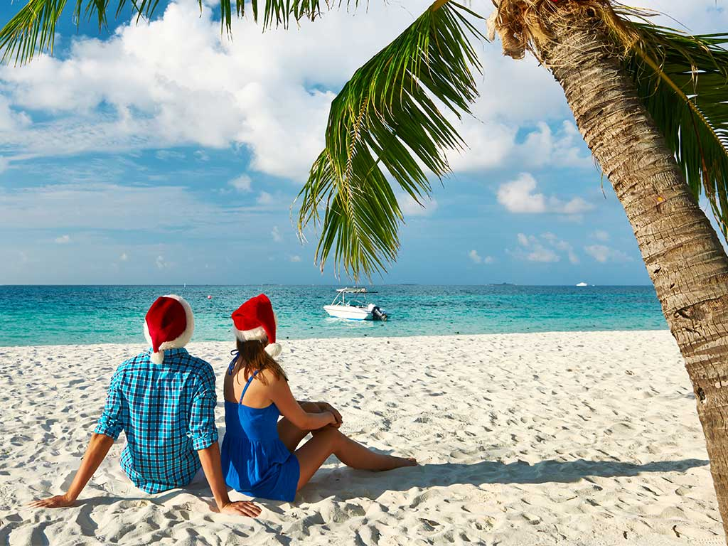Couple wearing Christmas hats sitting on a tropic beach under a palm tree