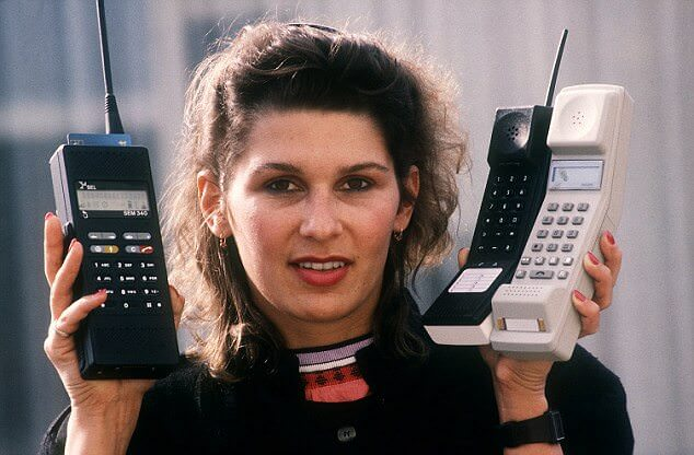 Woman holding three old mobile phones