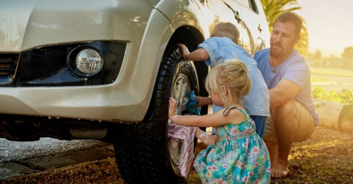 Father, daughter and son changing a car tyre