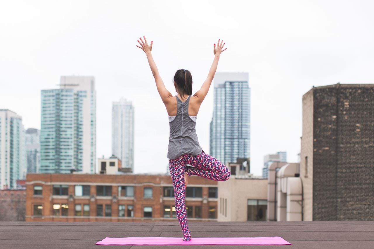 Woman doing a yoga pose on rooftop terrace