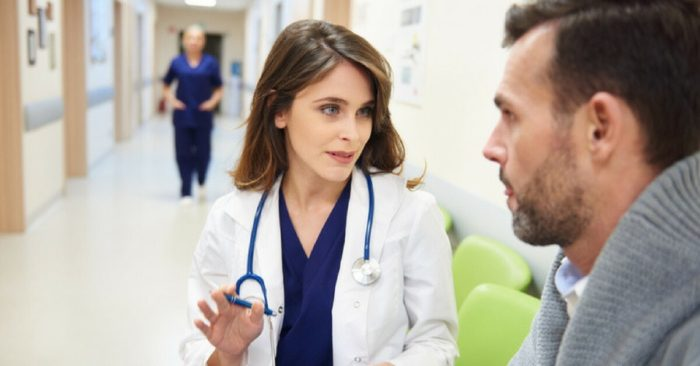 Young female doctor speaking with man