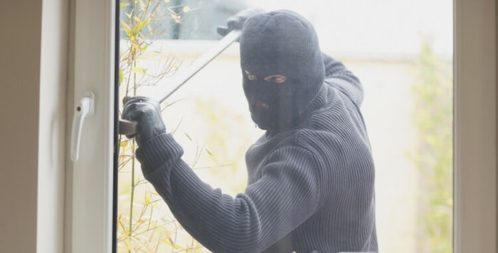 Man in balaclava trying to break into a home