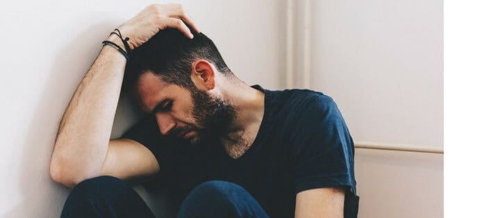 Man in corner of room feeling anxious