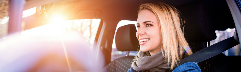 Smiling women focussed while driving on sunny day