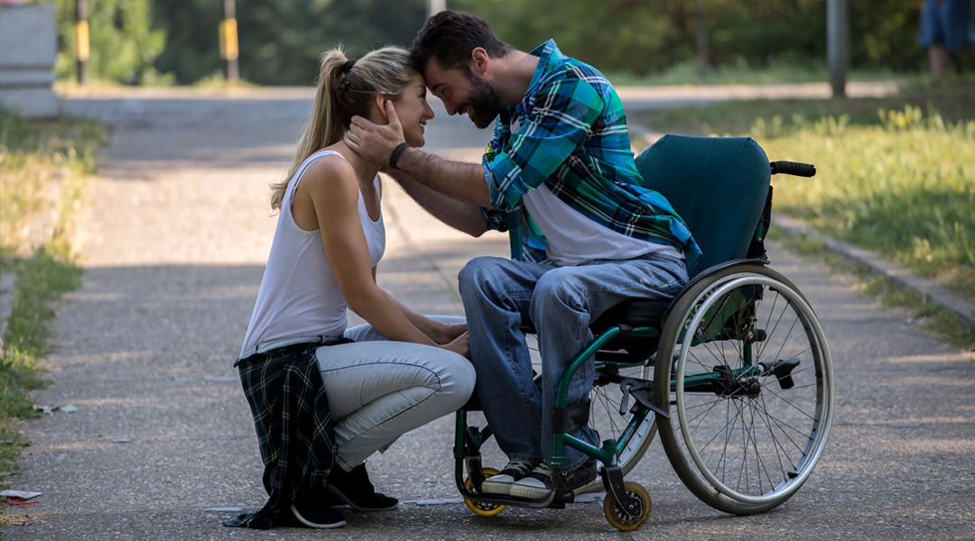 Man in wheelchair hugs his girlfriend