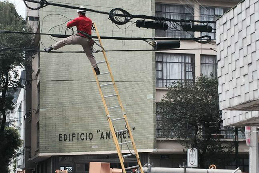 Man on step ladder working on electrical wire lines
