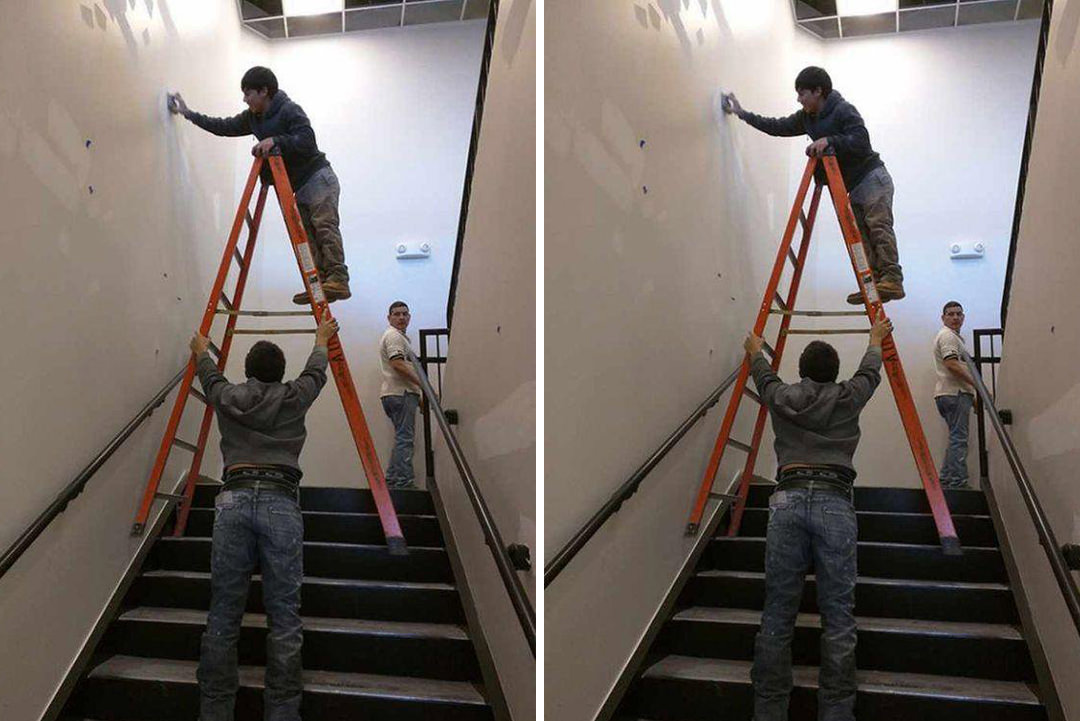 Man on step ladder, other man holding it on stairs