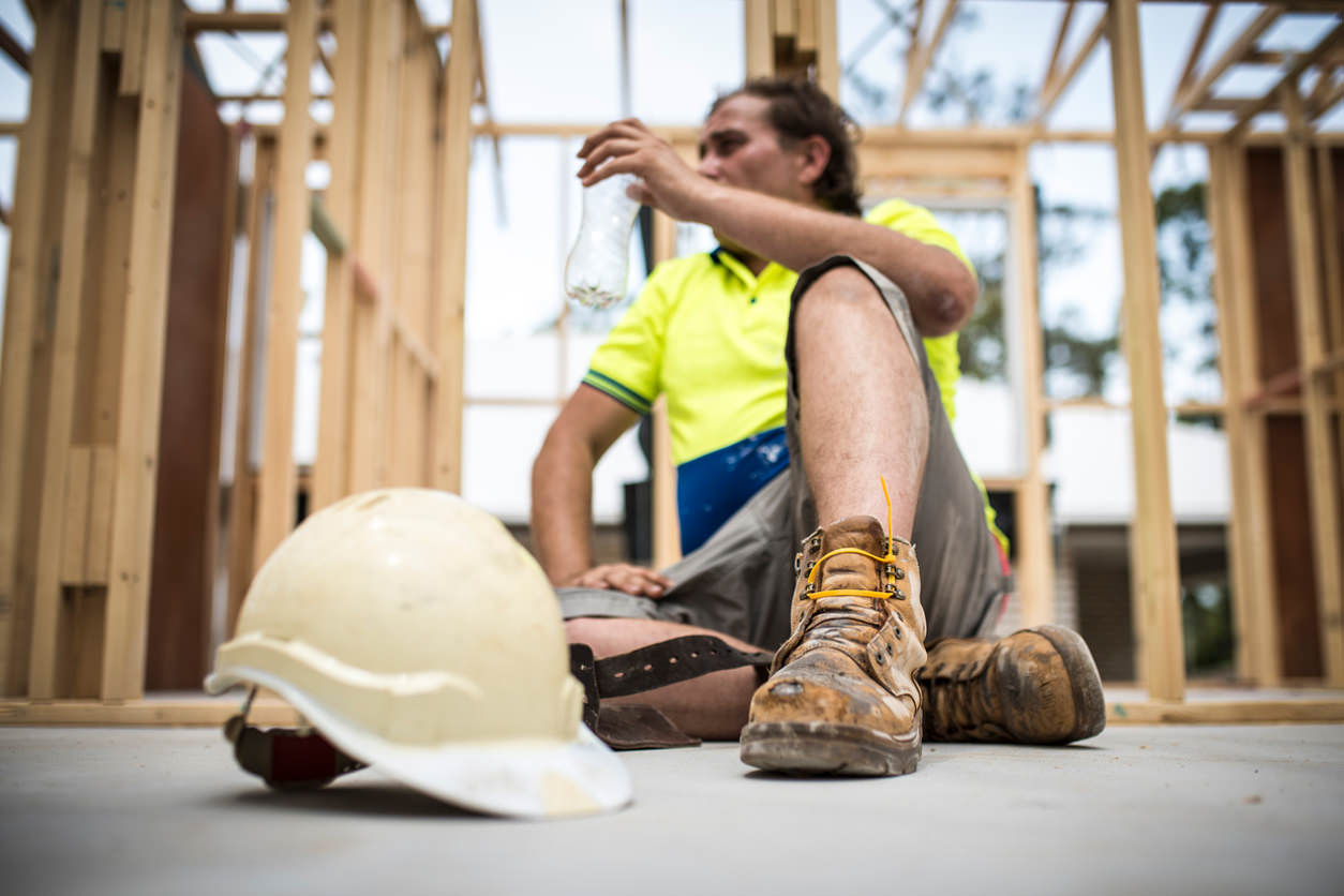 Tradie takes a break to drink water in construction site