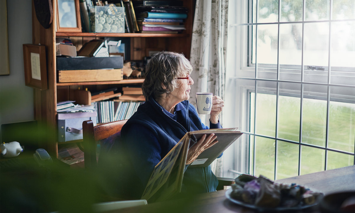 Aged woman having tea looking through a window
