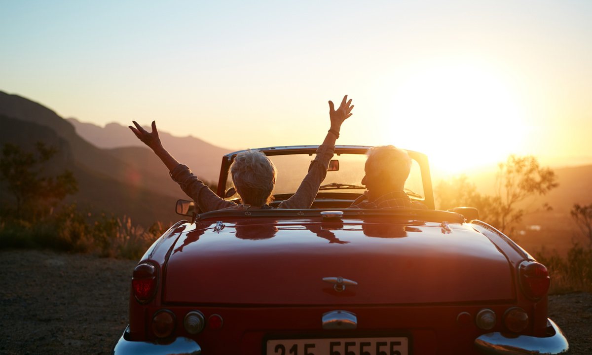Senior man and woman in sports car, hilly scenery