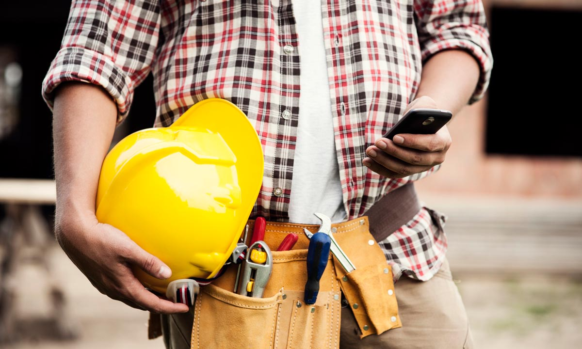 Person holding hard hat and mobile phone