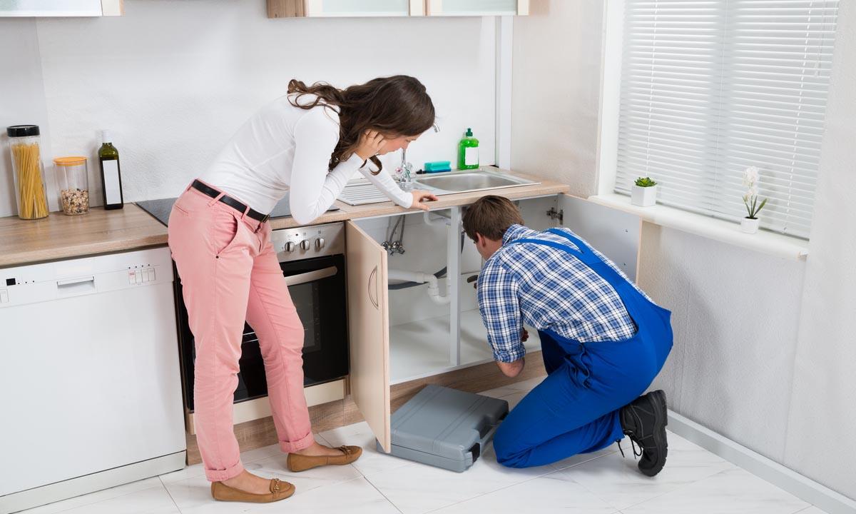 Lady watching plumber at work