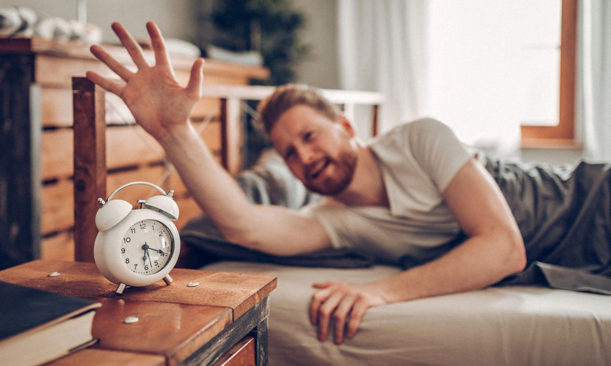 Man in bed about to turn off alarm clock