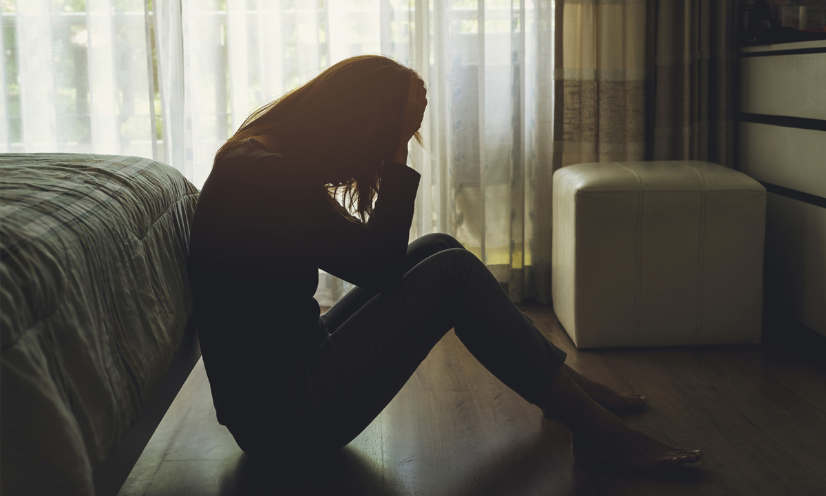 Depressed lady with hand in head in bedroom