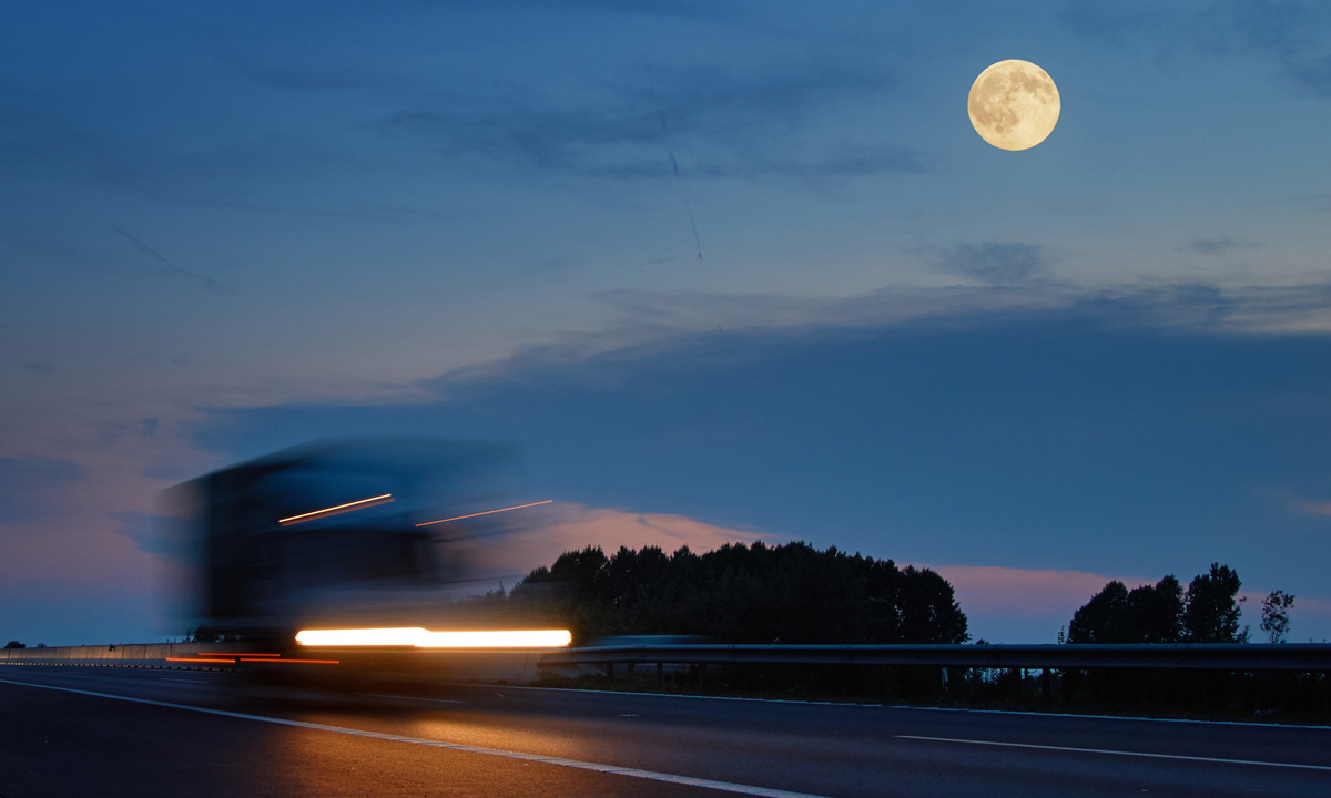 Moon, road and blurry truck