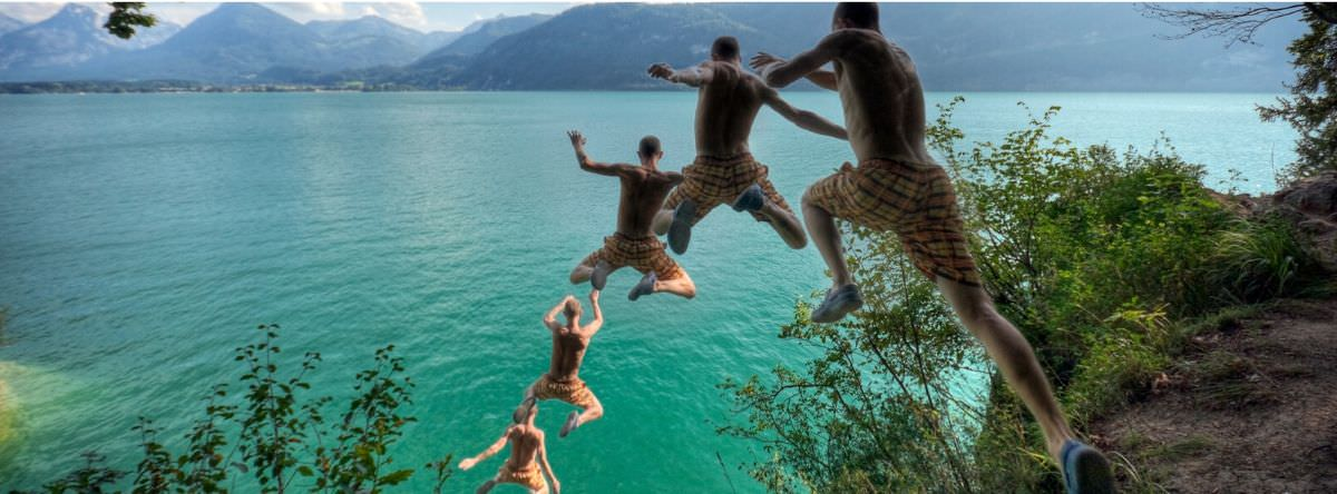 Young man jumping off cliff on holiday