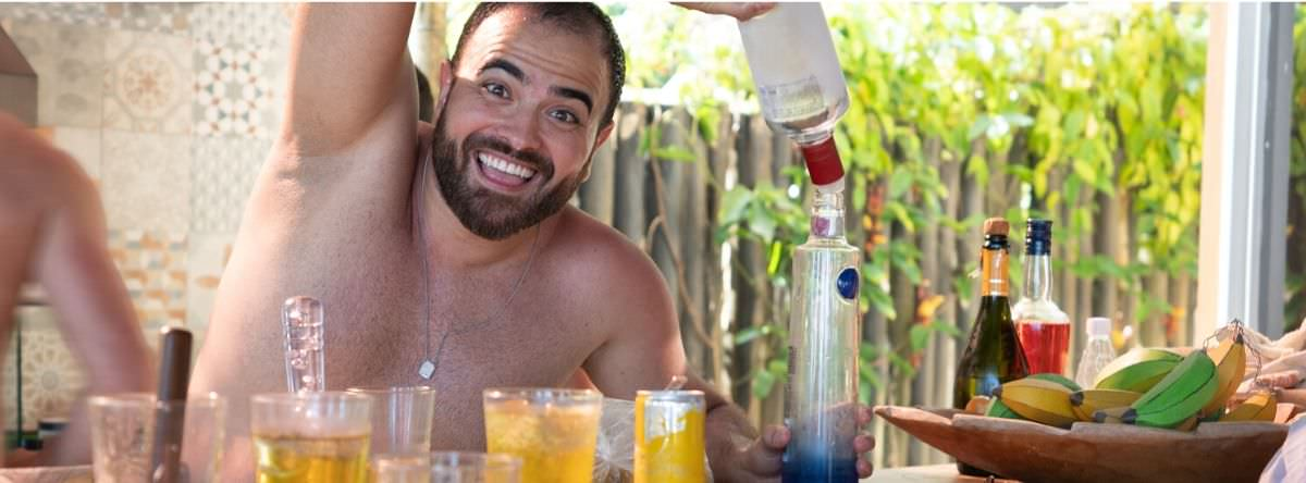 Man pouring drink and getting drunk on holiday