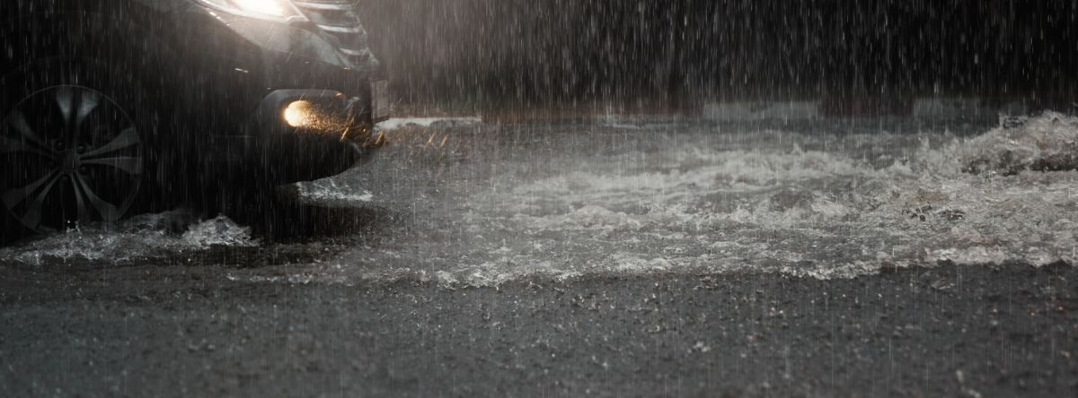 Car moving through puddles of water and pouring rain