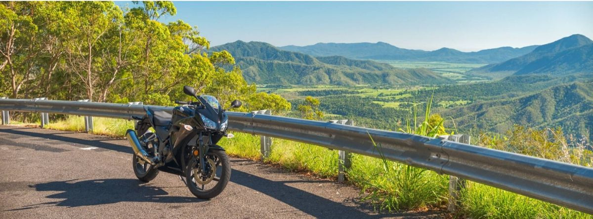 Motorcycle on the side of the road and hills scenery