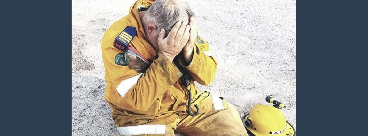 Firefighter clutching his face in grief