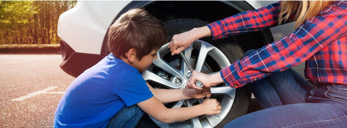 Kid and woman changing car tyre