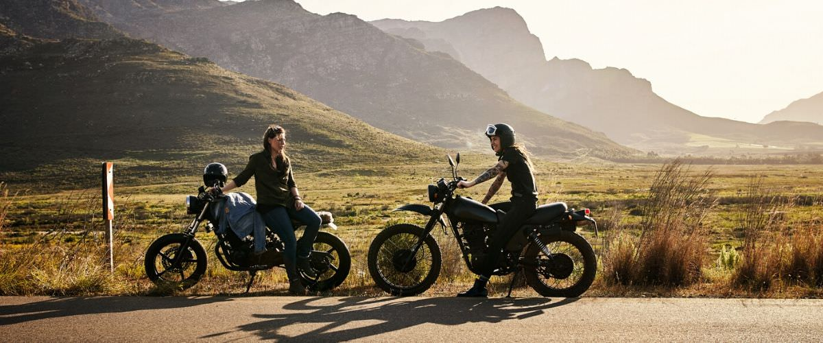 Two women enjoying the sisterhood of motorcycle riding in the mountains