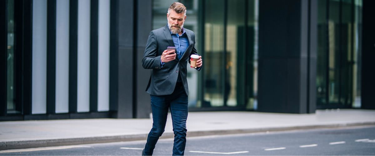 Jaywalking pedestrian holding a coffee and looking at his phone