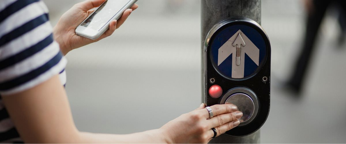 Lady pushes pedestrian crossing button with phone