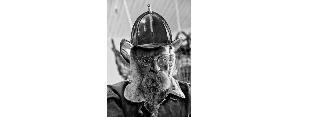 Black and white photo of man wearing fire hat with a big beard