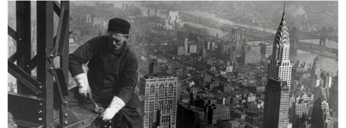 Black and white photo of a man working on a tall structure without any harness