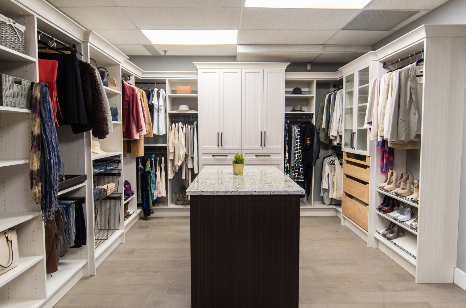 Luxury storage system, walk-in closet with drawers, cupboards, organizers, shelving and an island counter