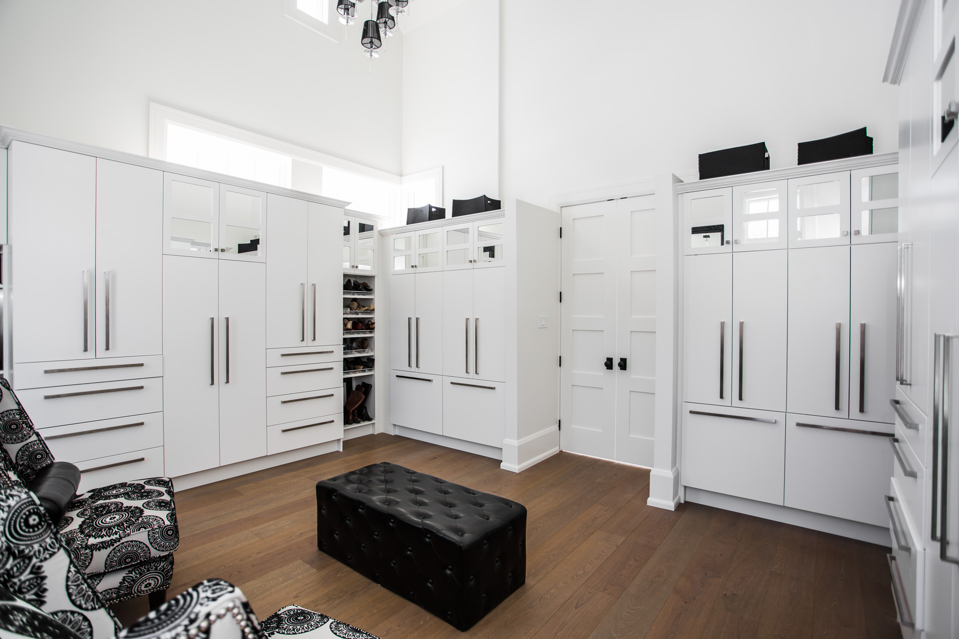 White walk in closet with crown moulding, mirror cupboards, doors, drawers, shoe rack, appliance pulls and baseboards
