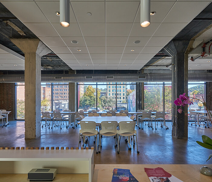 An industrial, open space with tables and chairs and large windows.