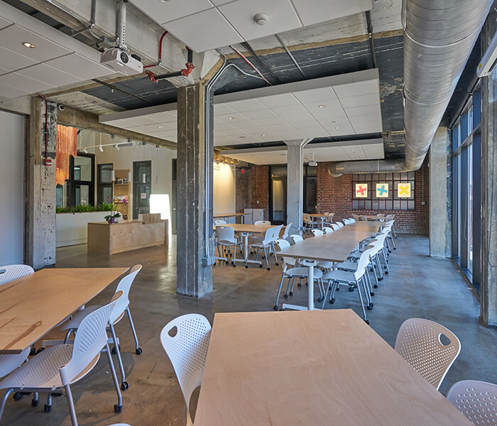 An industrial, open space with exposed brick and many tables and chairs.