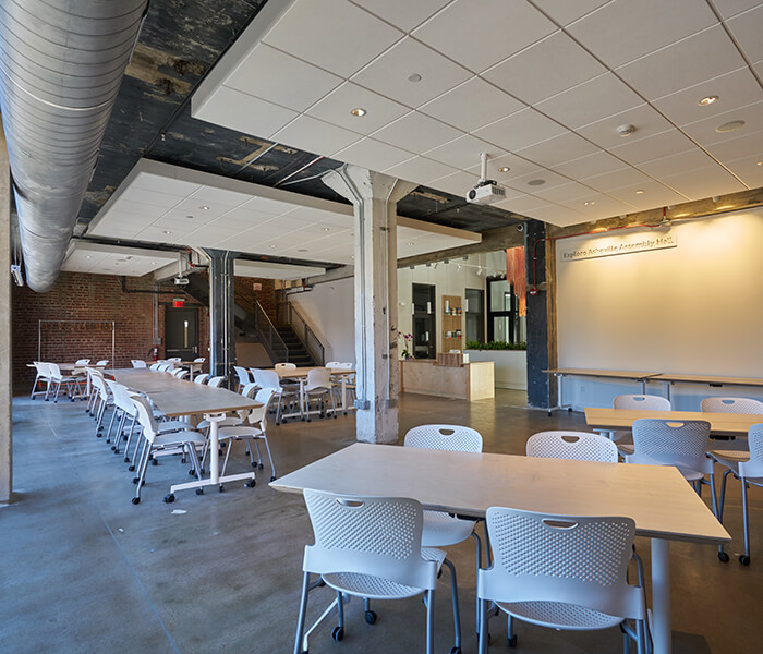 Large open space with white tables and chairs set up in the space.